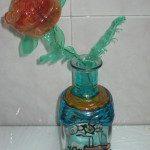 """Marta: Con una botella de licor y unas pinturas especiales para pintar en cristal se puede hacer un precioso jarrón para adornar el salón. Si luego le ponemos una flor hecha con plástico y alambre queda todo muy """"reciclado""""."""